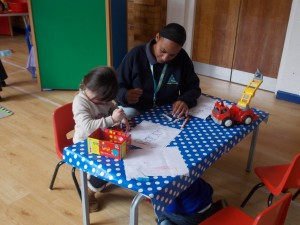 Child drawing with teacher