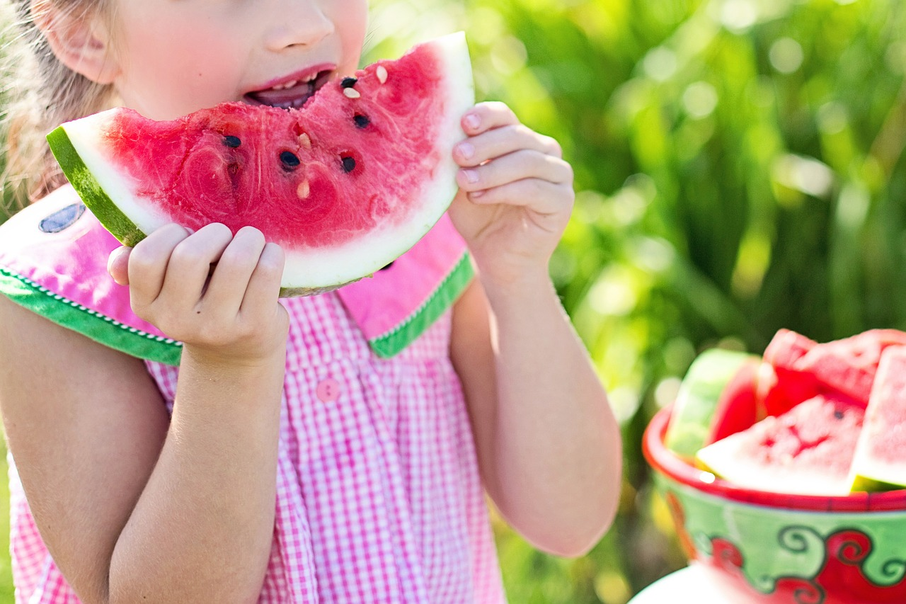 A girl eating a slice of watermelon