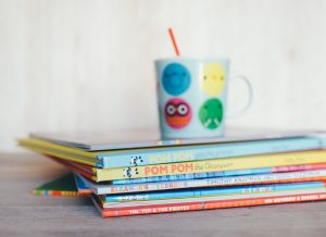 A pile of young children's book with a smiley-face mug on top
