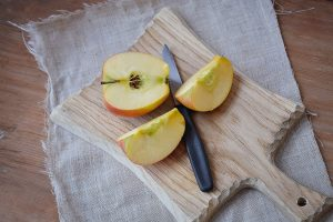 An apple cut in pieces on a board with a knife